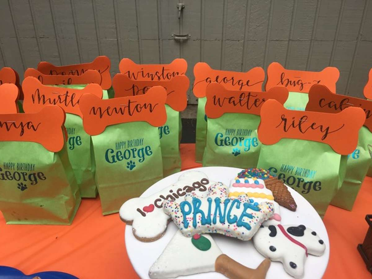 personalized goodie bags with a dog bone and calligraphy names for a dog party with dog themed cookies