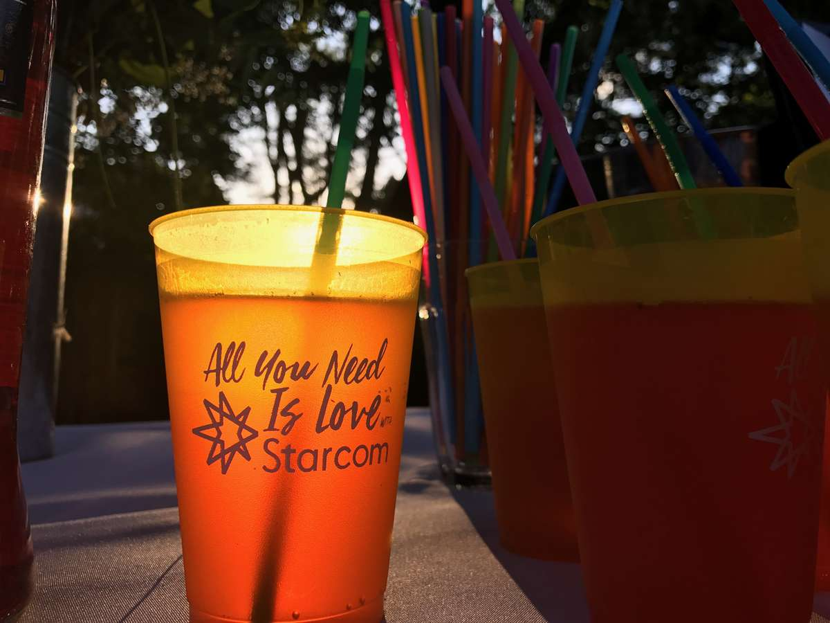 personalized plastic cups with colorful straws for an outdoor party