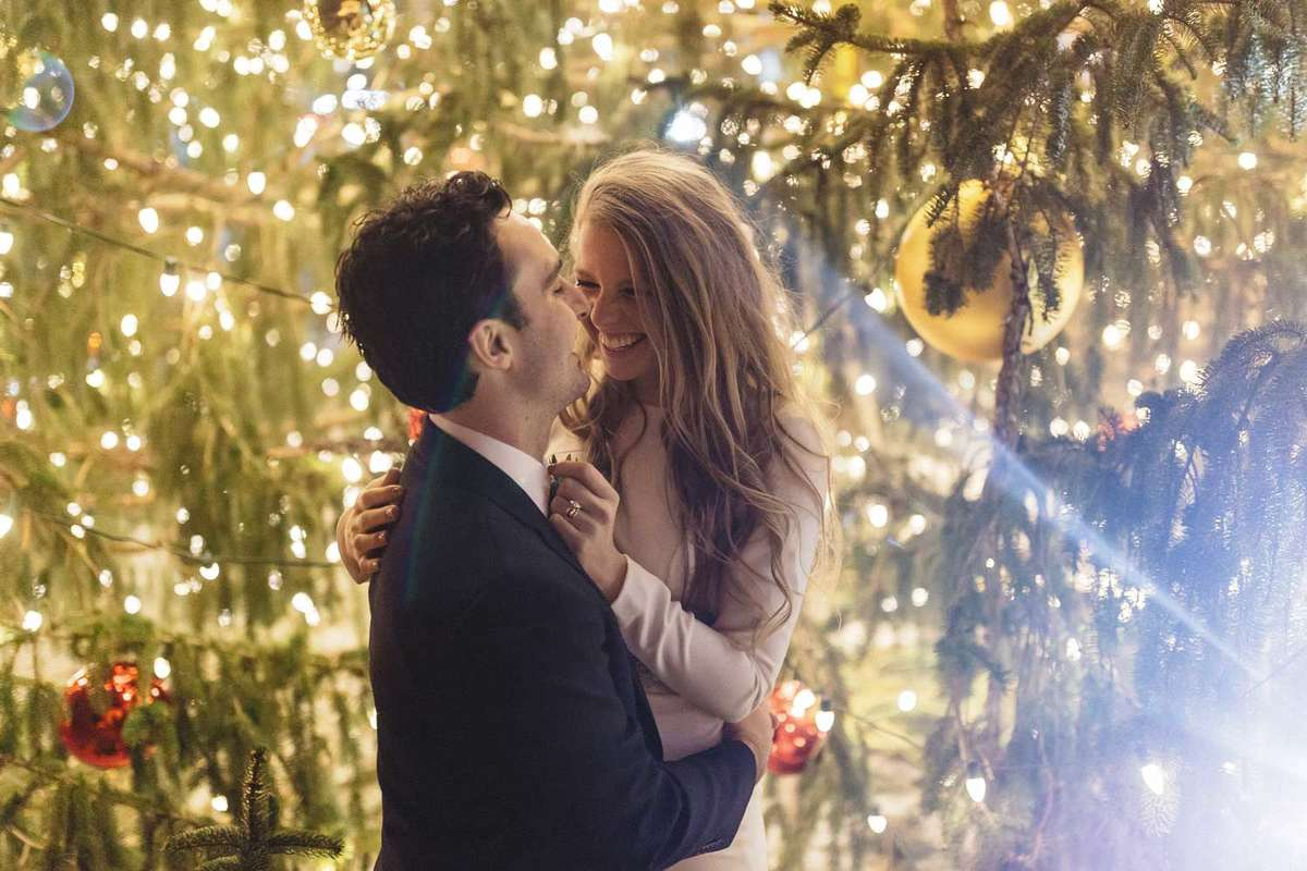 winter wedding bride and groom with christmas tree