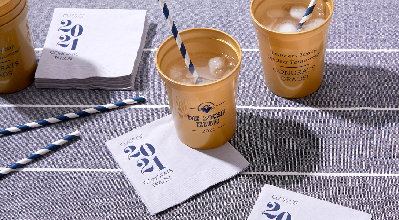 Gold Stadium Cup and white cocktail napkin with graduation design in Navy blue ink and foil