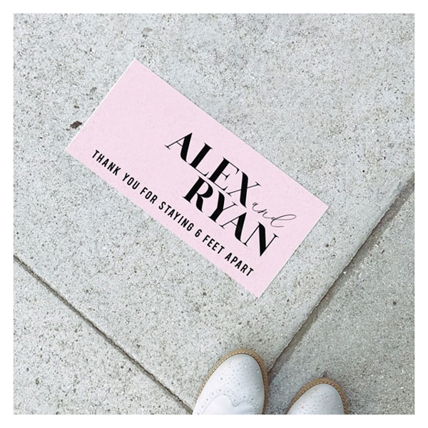 Pink digitally printed vinyl rectangle floor sign that includes couples names in black block font