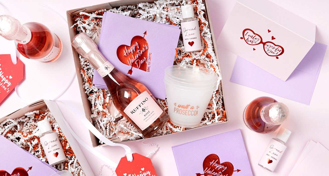 Box with mini champagne bottle, valentines day themed napkins, tags and cards, and party ready disposable frost flex cups